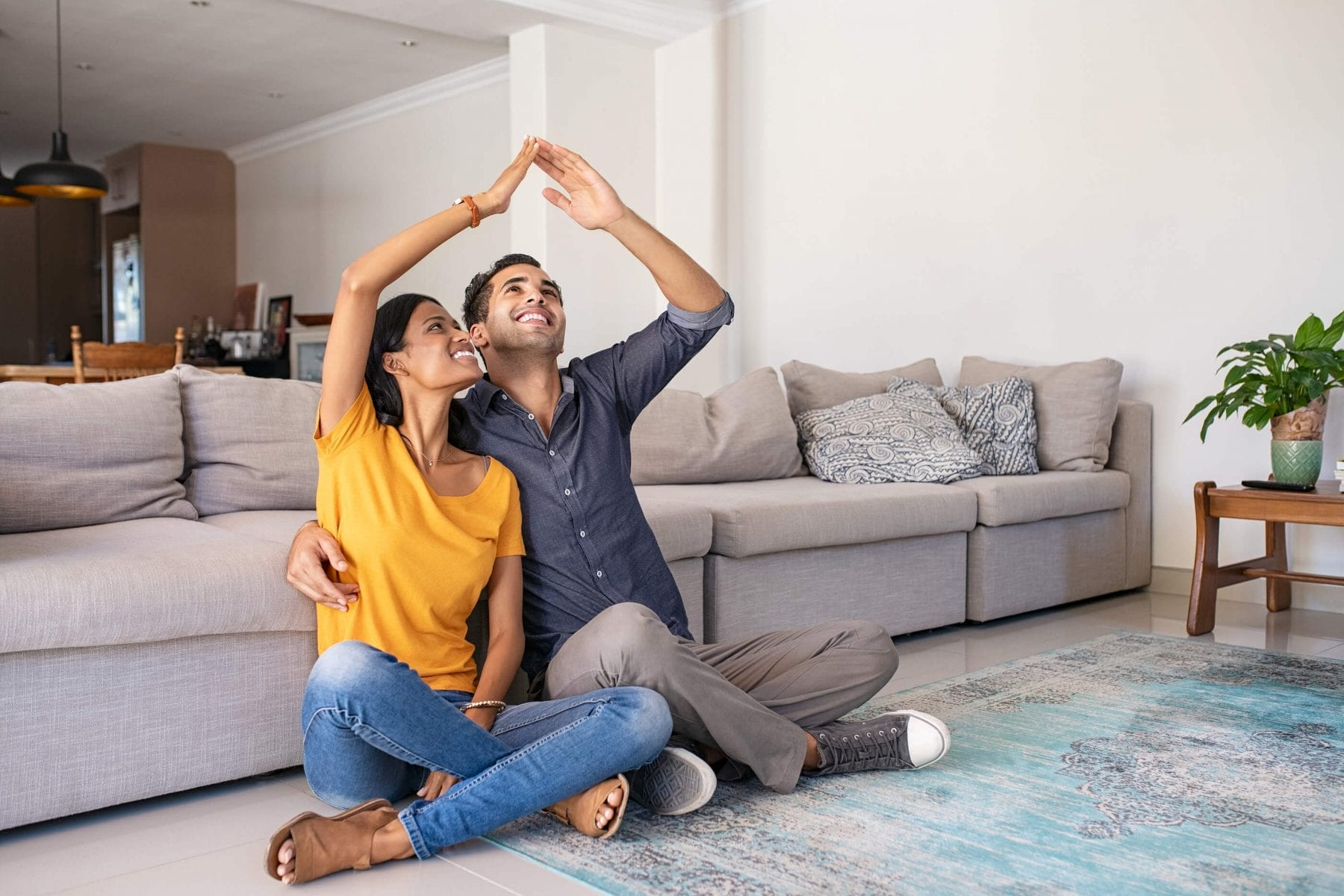 South Asian couple sitting on the floor in living room dreaming of homeownership